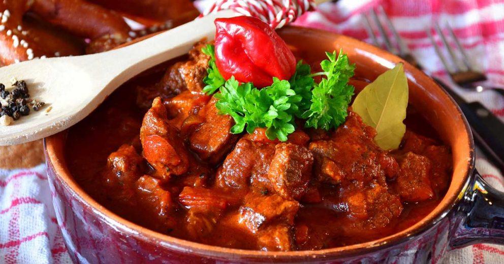 maďarský gulás na tanieri s drevenou lyžicou a chilli